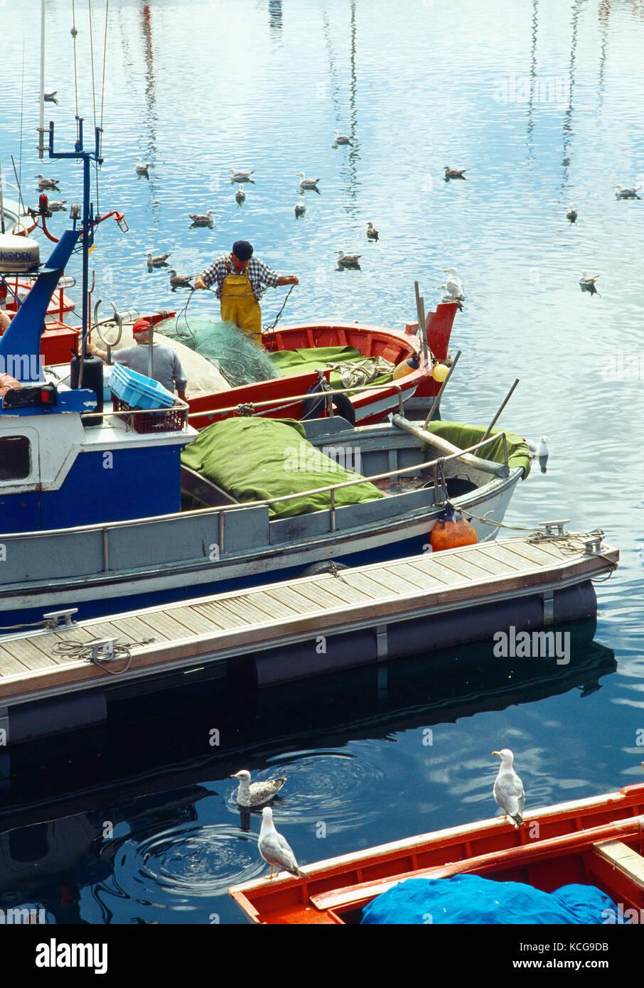 Fishermen working on their fishing boat. Harbour, La Coruña, Galicia, Spain. - Stock Image