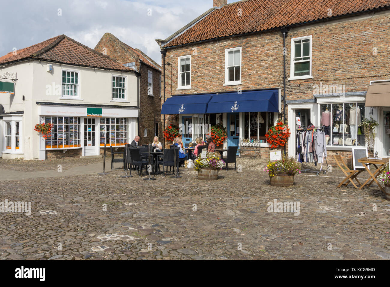 A view aross the square in the market town of Easingwold with people sitting outside the Tea Hee café; Yorkshire, - Stock Image