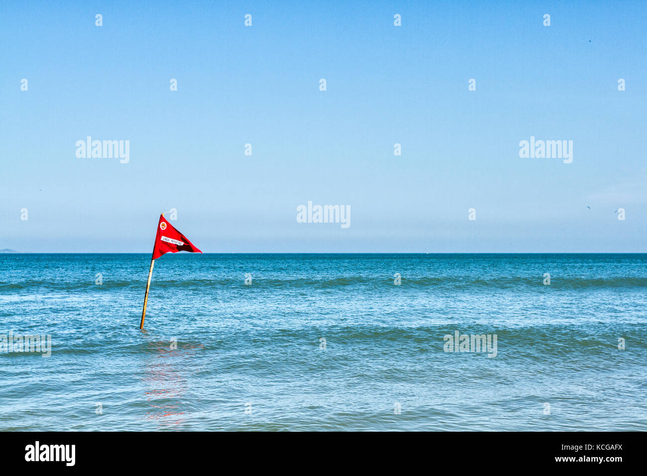 Red flag in the water indicating dangerous constions at Acores Beach. Florianopolis, Santa Catarina, Brazil. - Stock Image