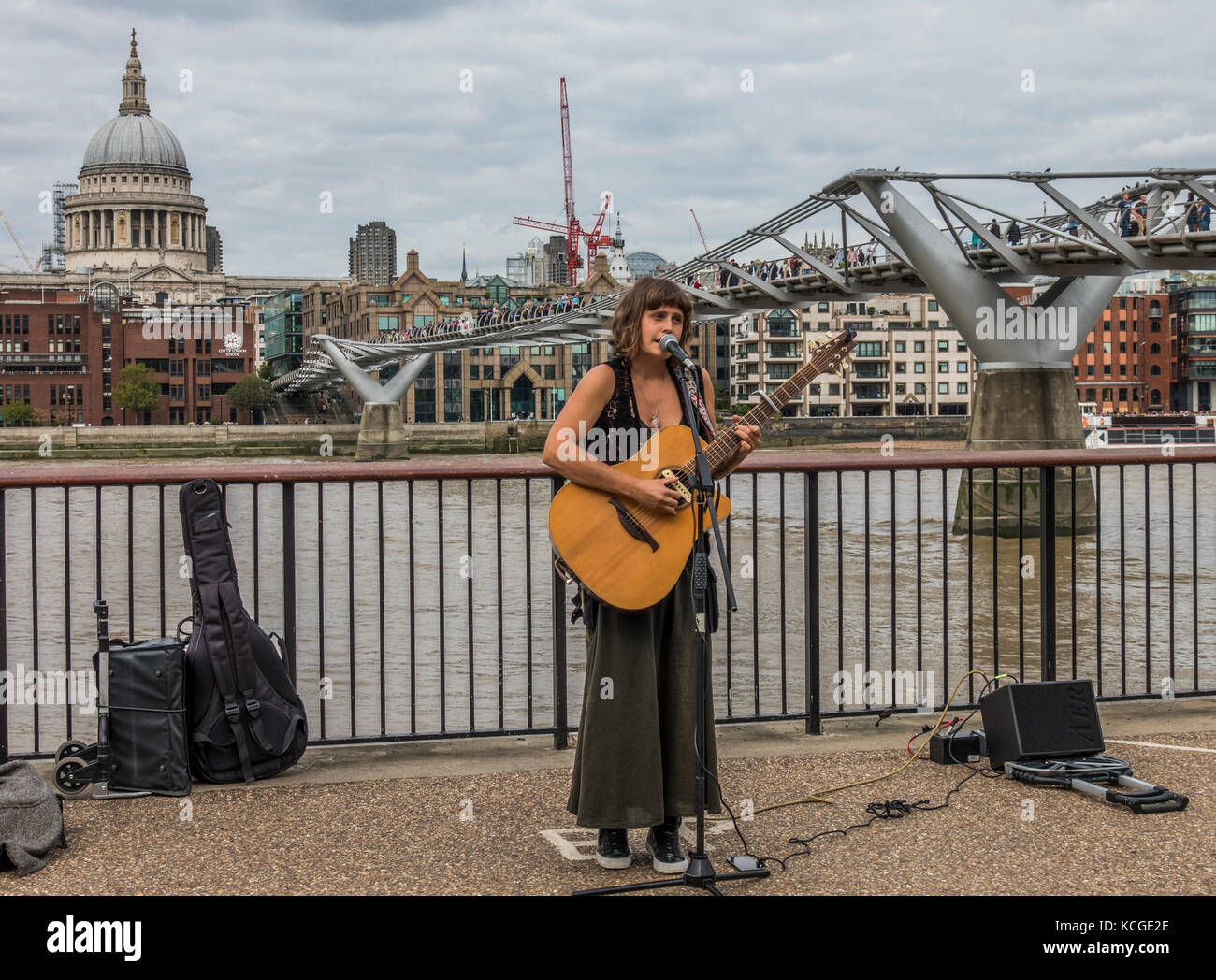 A young woman busker, singing and playing acoustic guitar, with microphone and portable amplifier, next to the Millennium - Stock Image