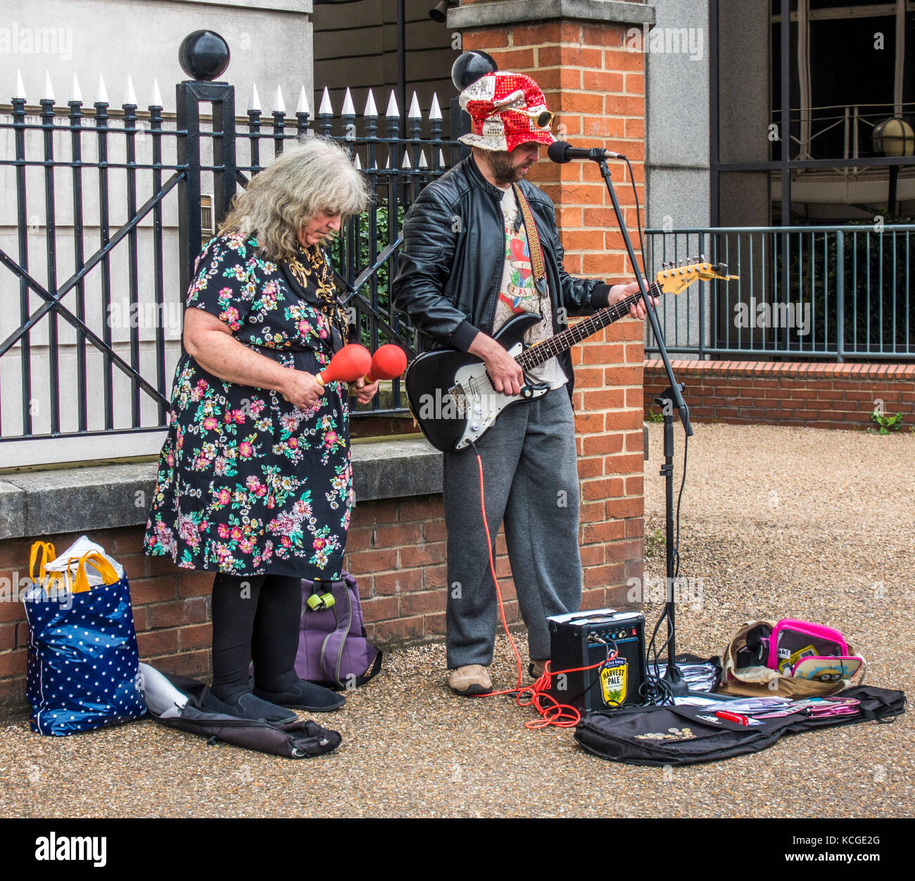 Eccentric busker / buskers: older woman and man, playing electric guitar, with microphone, amplifier and maracas. - Stock Image