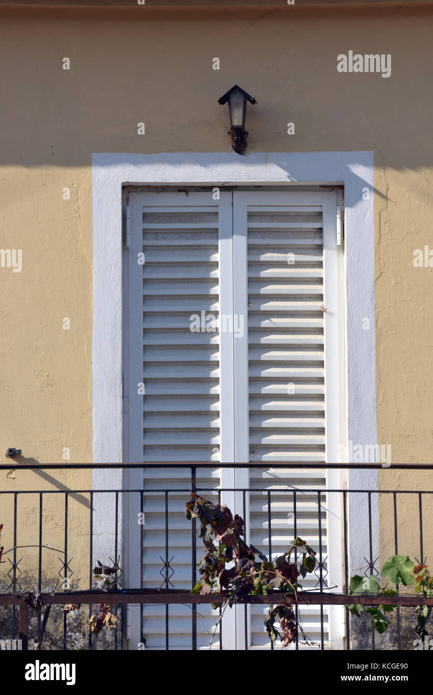 a typical greek balcony with cast iron railings, a Juliet balcony and white painted shuttered doors to give shade - Stock Image