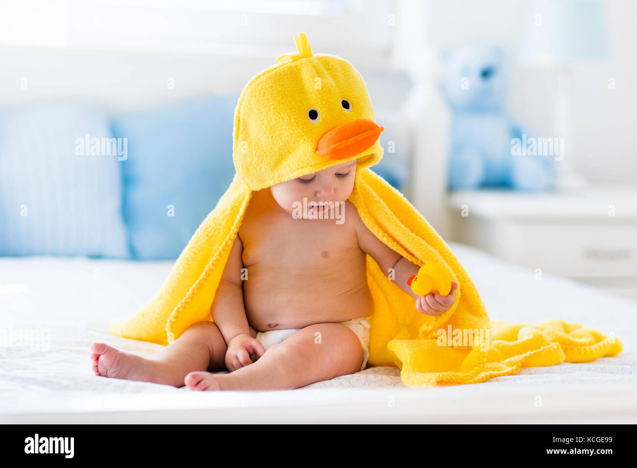 221ca9524 Happy laughing baby wearing yellow hooded duck towel sitting on ...