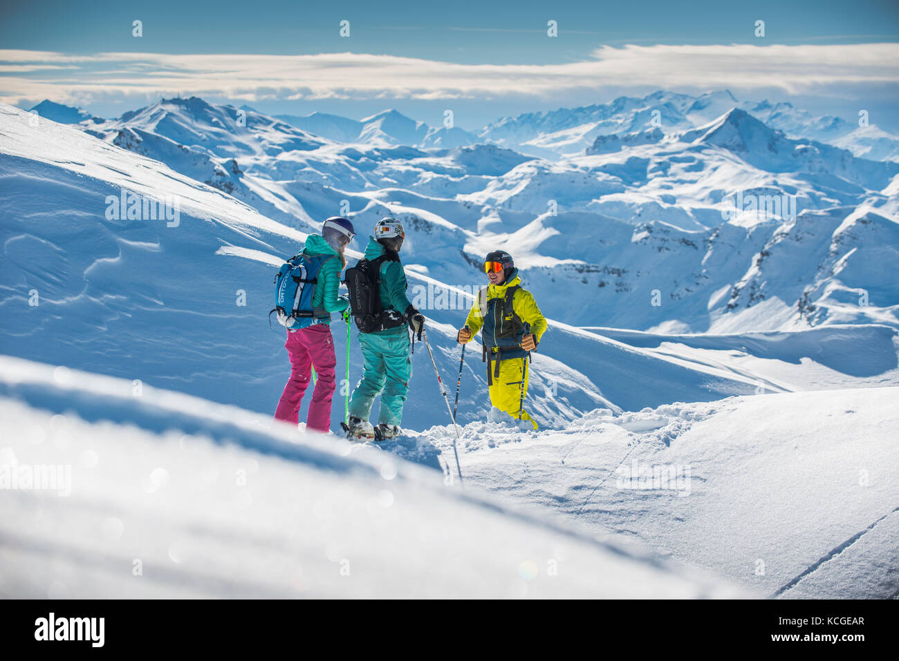 A ski instructor guides two women off piste in the French ski resort of Courchevel. - Stock Image