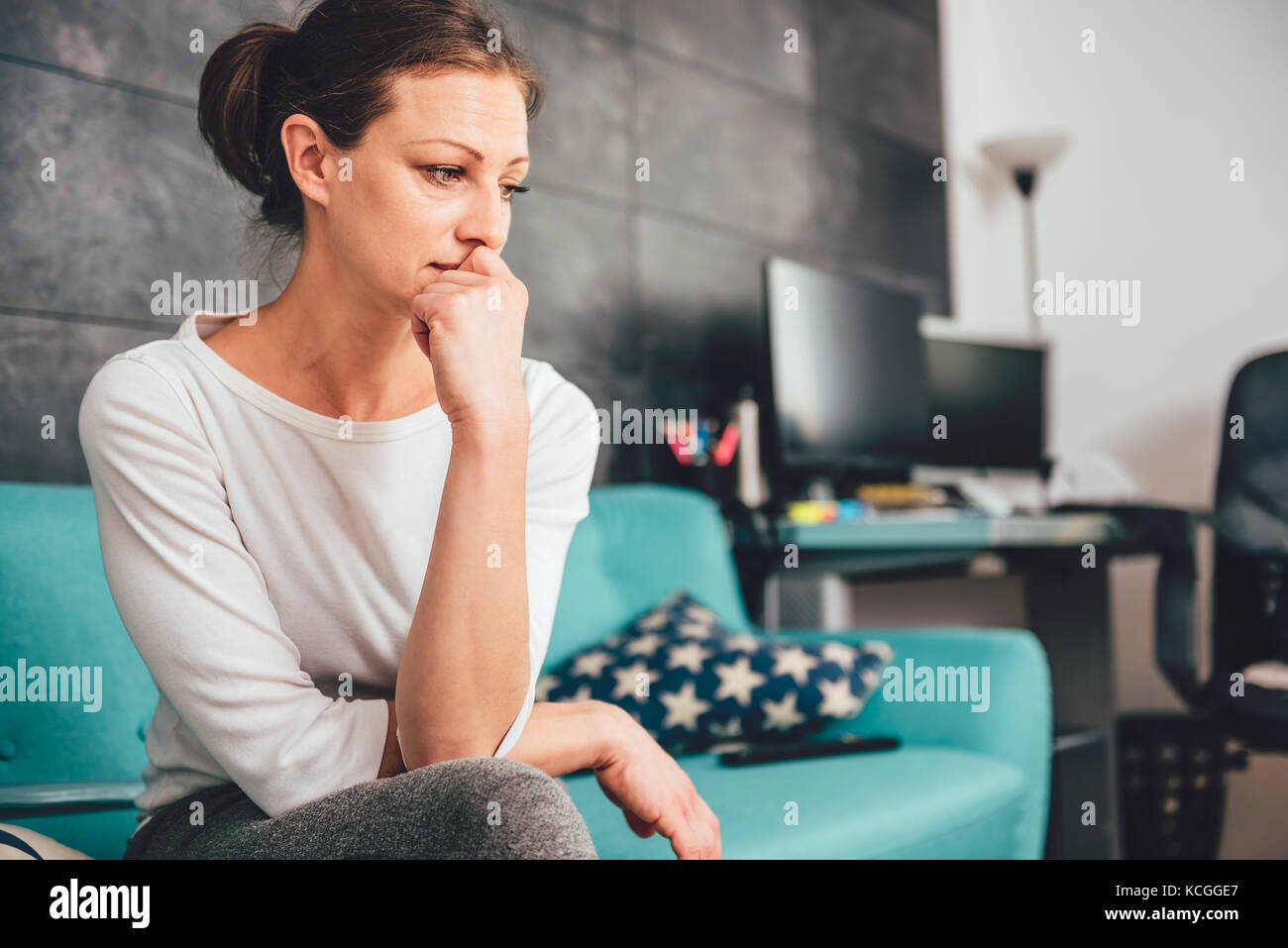 Sad woman sitting on a sofa in the living room - Stock Image