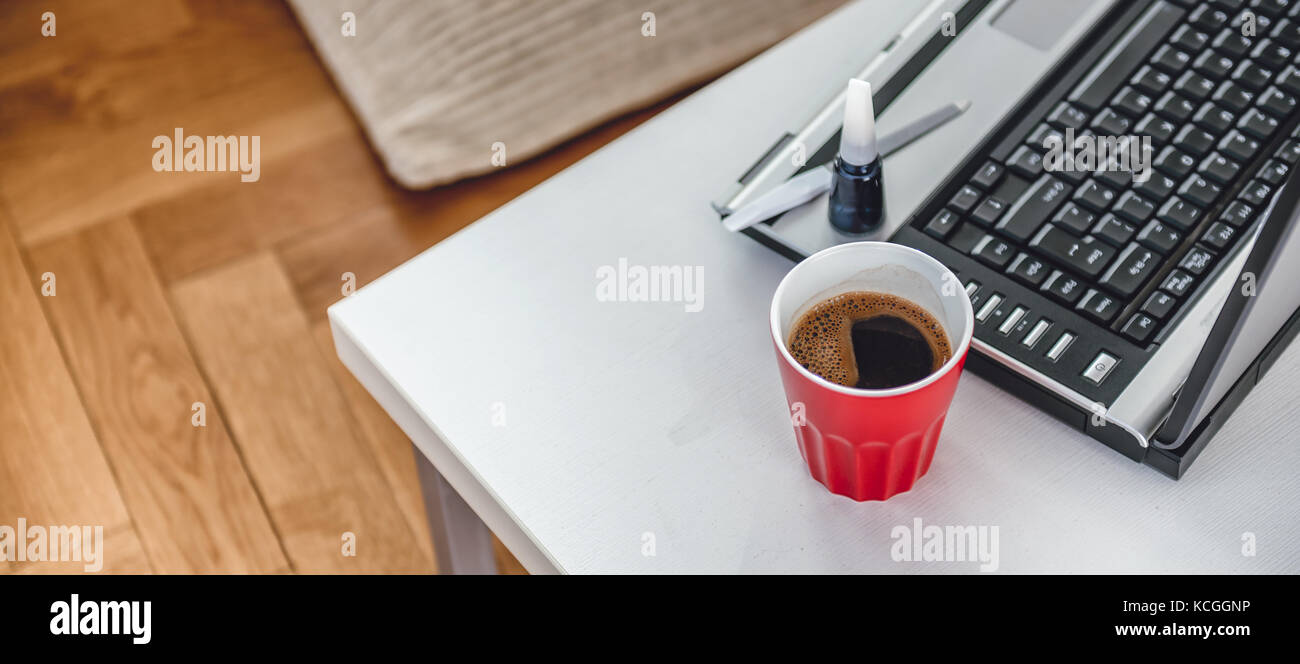 Red Coffee cup, Nail Paint and laptop on the coffee table - Stock Image