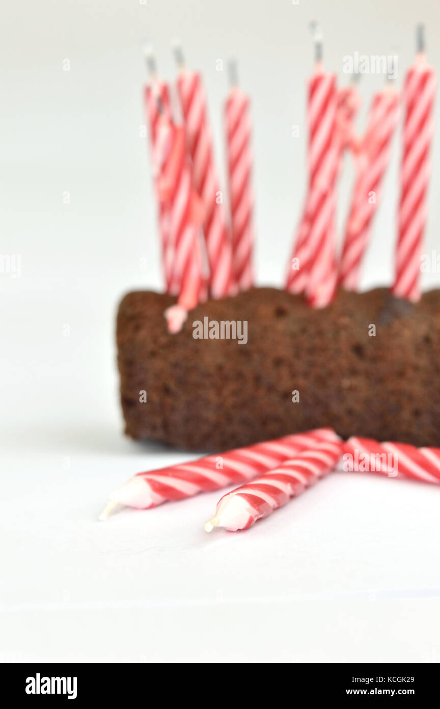Closeup of some candles on the fround and a birthday cake in the blurred background - Stock Image