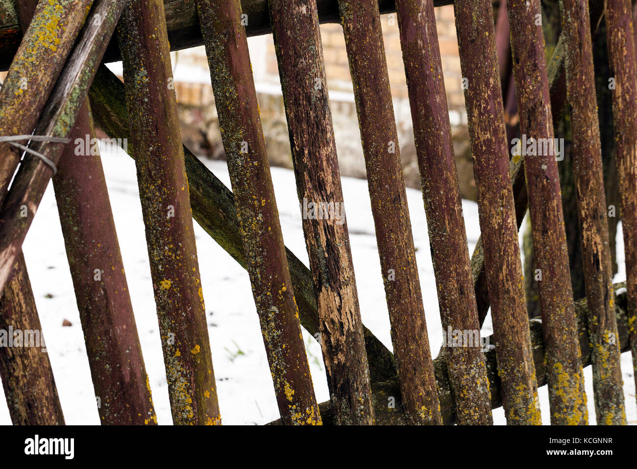an old destroyed wooden fence in the countryside. Part of the fence is broken. Photo taken close up - Stock Image