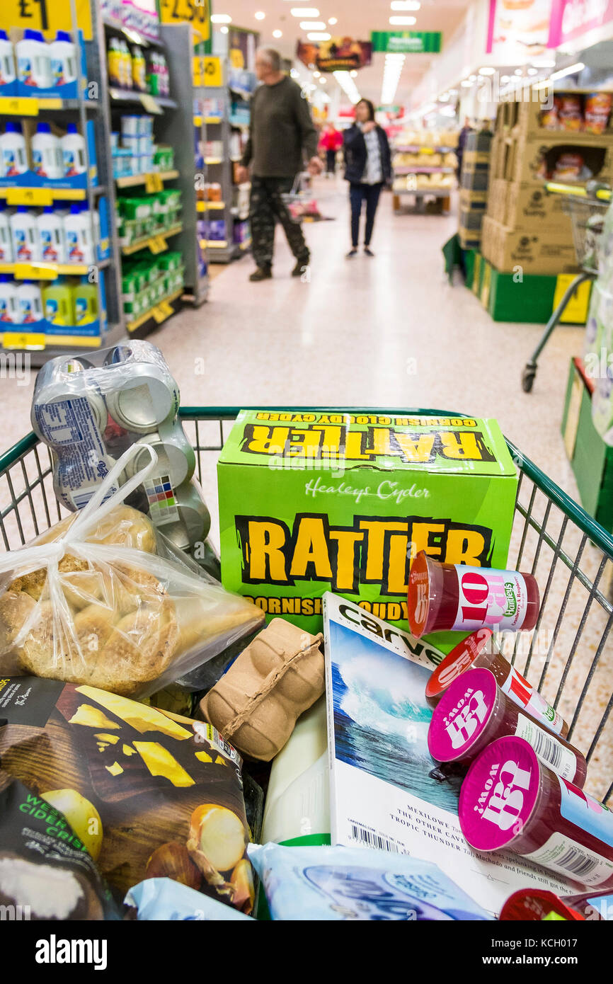 Shopping in a supermarket - a shopping trolley full of items bought in a Morrisons Supermarket. - Stock Image