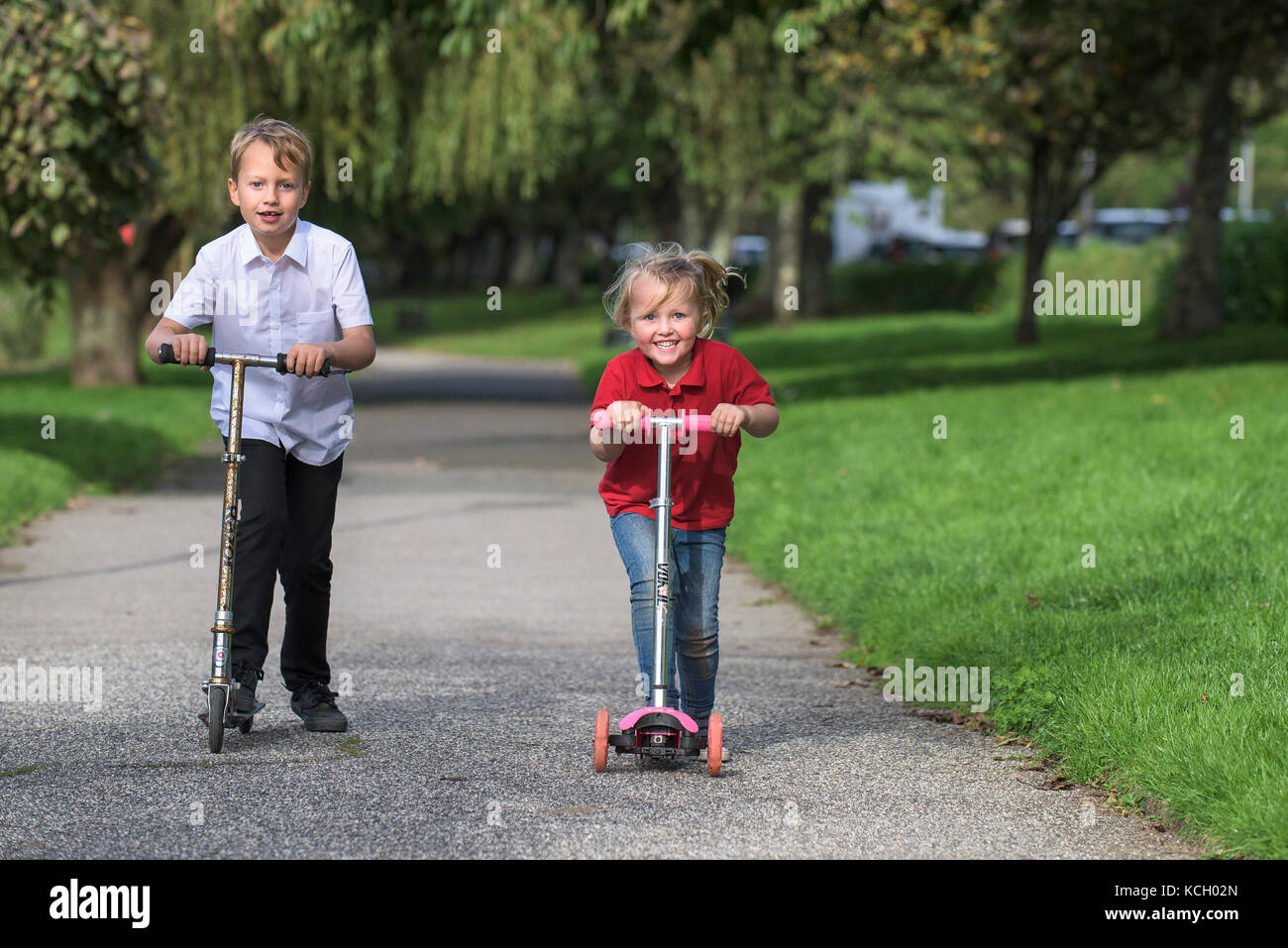 Children riding their scooters - a young boy and his young sister having fun racing along a path on their scooters. - Stock Image