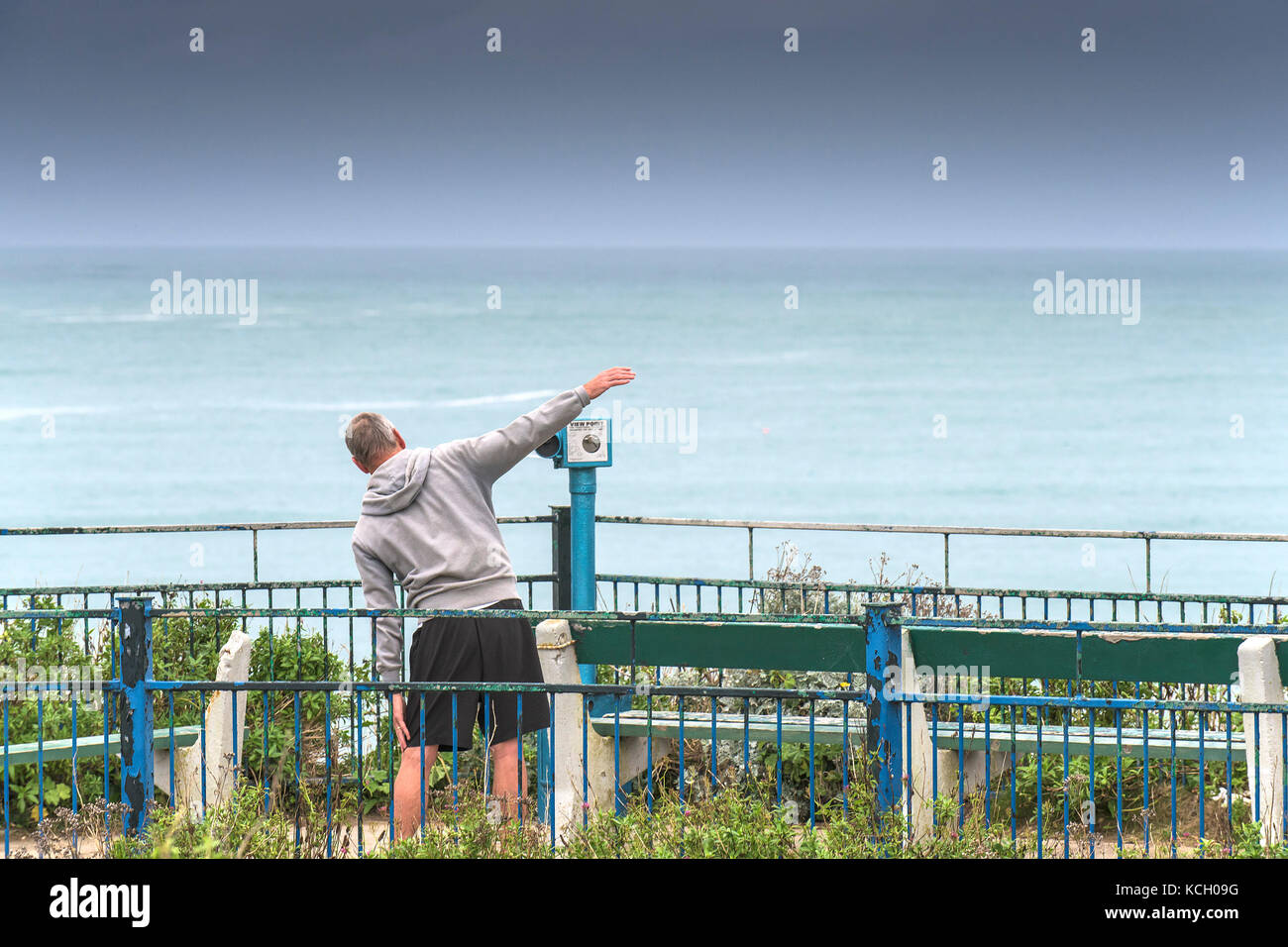 Early morning workout - a man exercising in a seating area overlooking the sea in Cornwall. - Stock Image