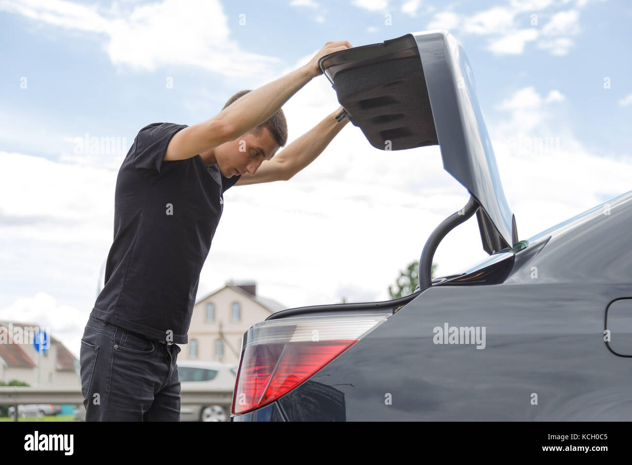 Car broke down on the way. The man opened the trunk to take the tools. - Stock Image
