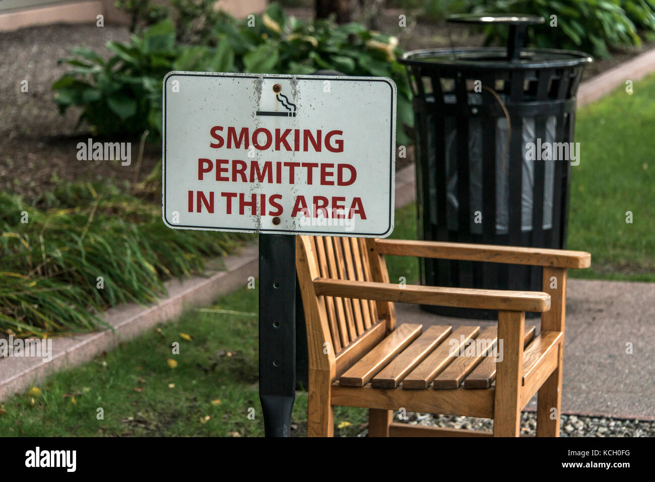 Designated smoking area Outdoor bench in smoking zone permitted - Stock Image