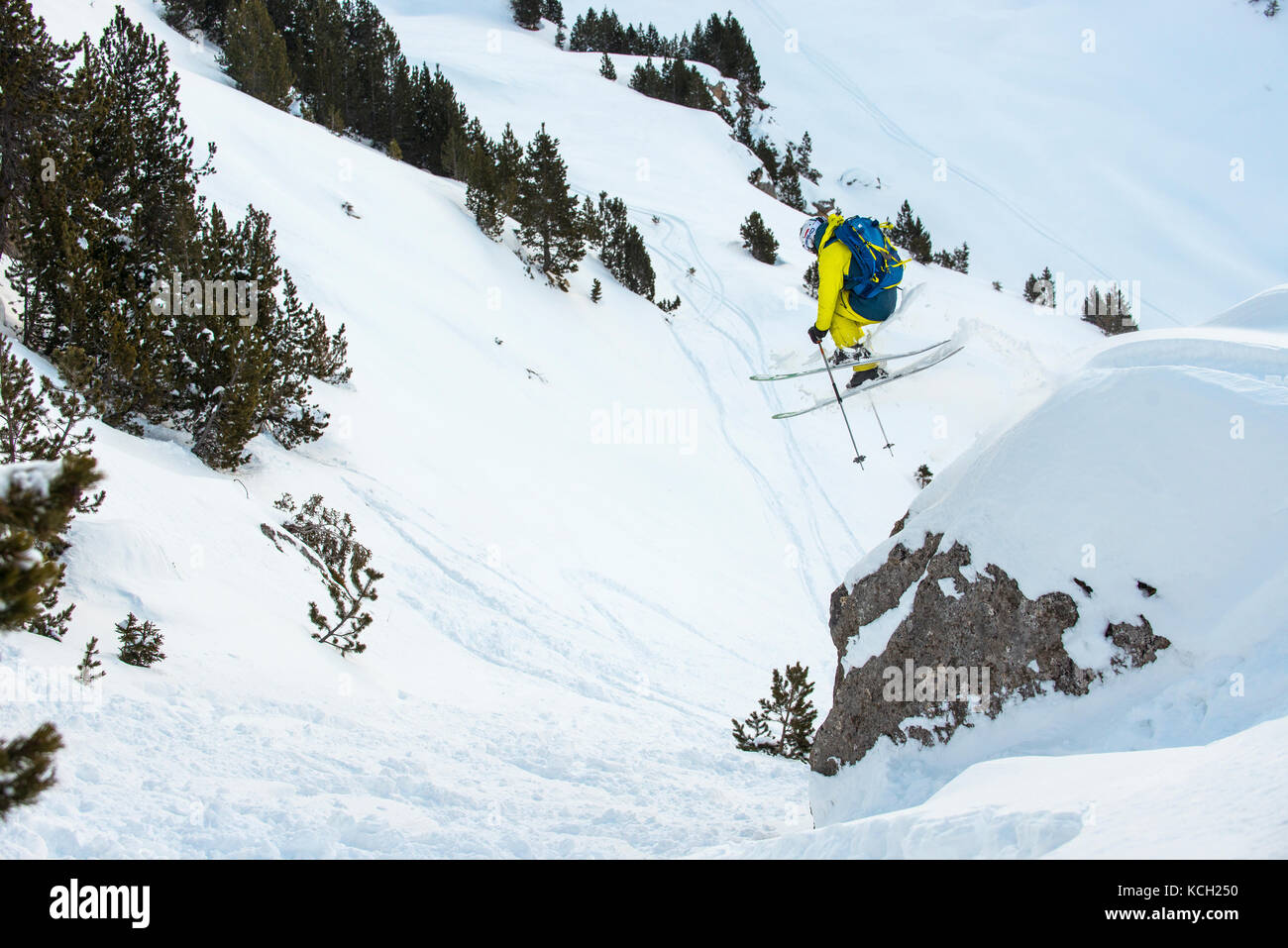 A skier jumps off a rock off piste in the French alpine resort of Courchevel. - Stock Image