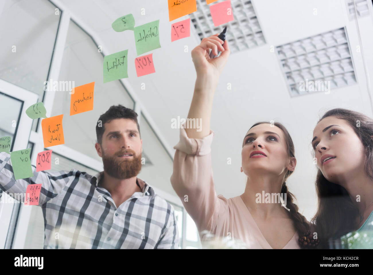 reliable young workers posting reminders in a modern co-working  - Stock Image