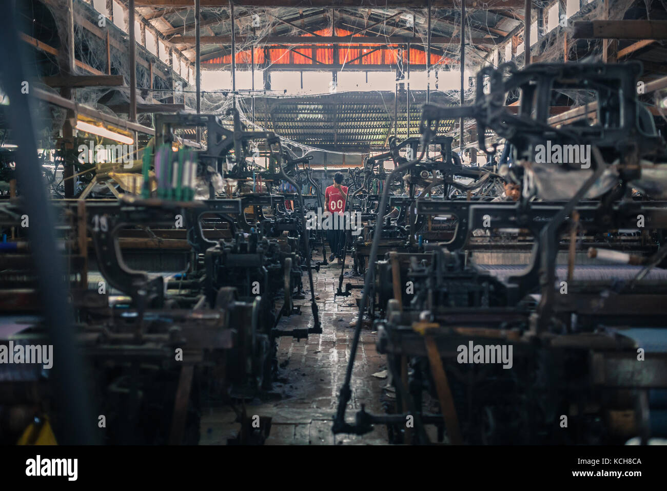 MANDALAY, MYANMAR - JANUARY 11, 2016: Unidentified man in a small silk factory on the outskirts of Mandalay, Myanmar - Stock Image