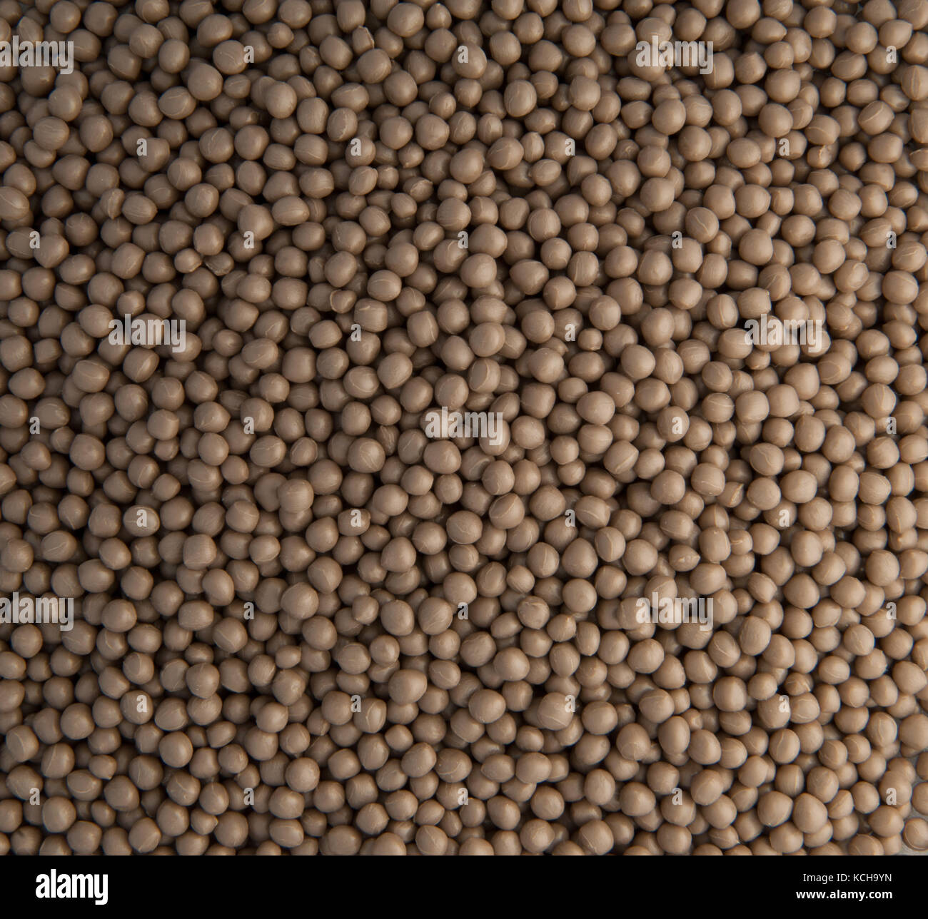 background of small plastic pellets brown colored - Stock Image
