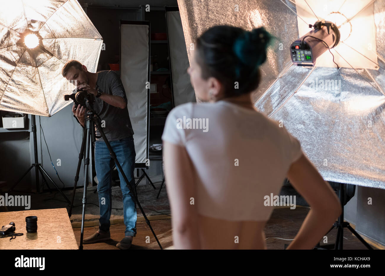 photographer in the process of shooting a model in a photo Studio Stock Photo