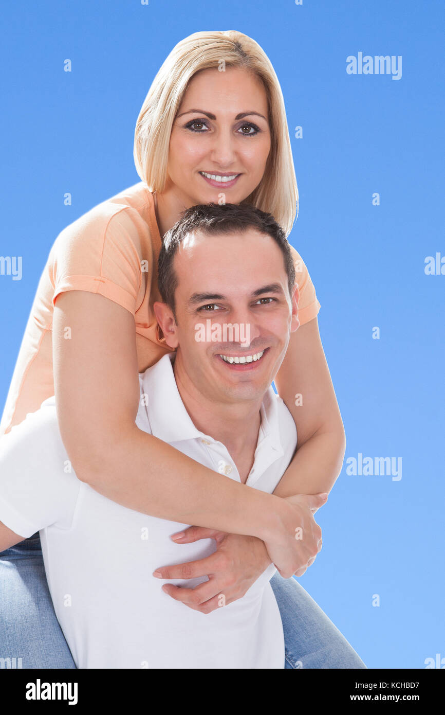 Happy Man Piggybacking His Girlfriend Against Blue Sky - Stock Image