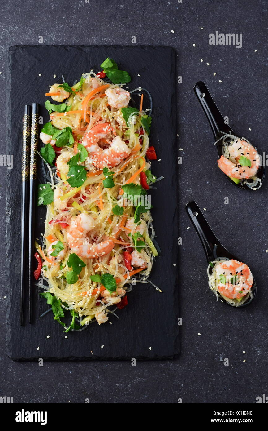 Noodles with prawns and vegetables on a black stone plate and in traditional soup spoons on a grey abstract background. - Stock Image