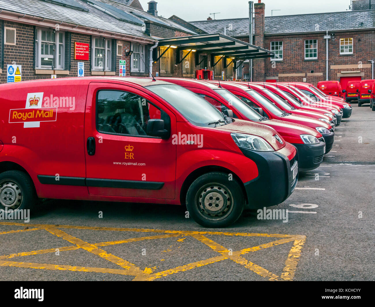 Line of Red Royal Mail Vans In Depot - Stock Image