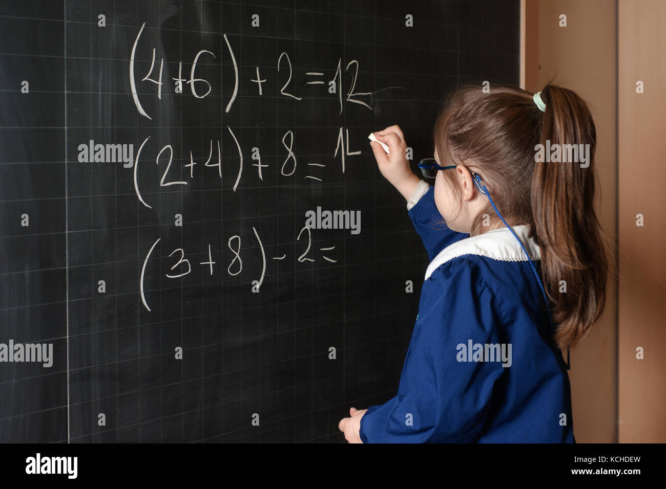 Italian elementary school girl first-grader solve mathematics examples. The student thinks and feels near the Board. - Stock Image