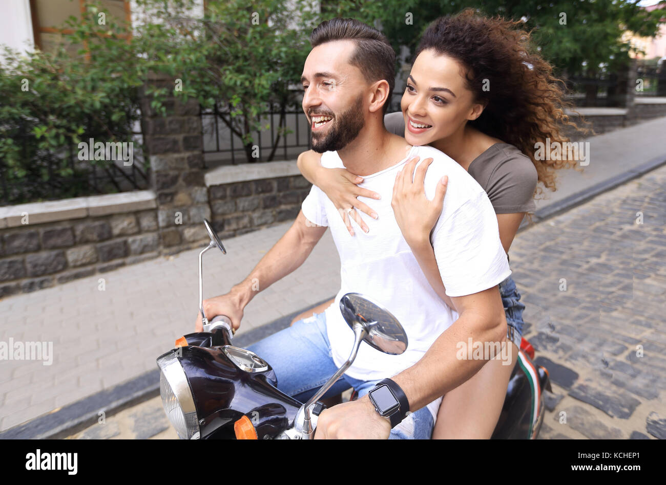 Young couple riding motor scooter in city - Stock Image