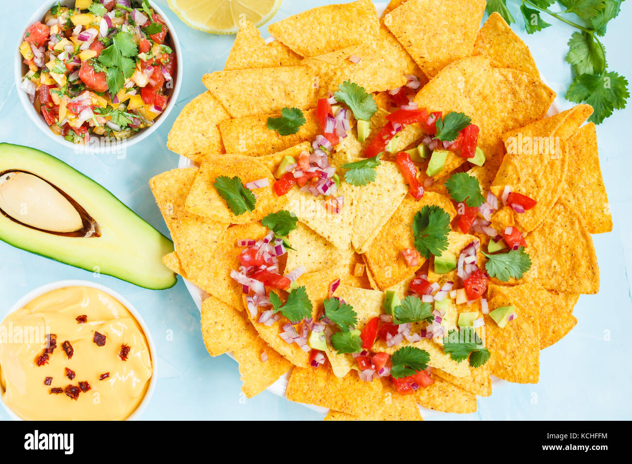 Yellow corn chips nachos with cheese sauce and salsa sauce. Mexican food snack concept. - Stock Image