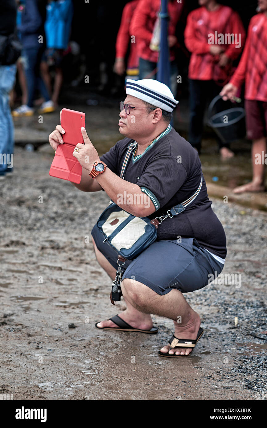 Taking photo with tablet. Using iPad to take photograph. People squatting. Crouching down. - Stock Image