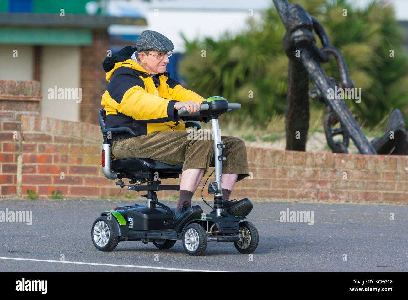 Elderly man riding on an electrically powered mobility scooter, in the UK. - Stock Image
