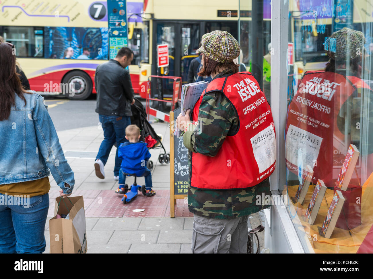 Woman on the streets as an official vendor of the Big Issue magazine in Brighton, East Sussex, England, UK. - Stock Image
