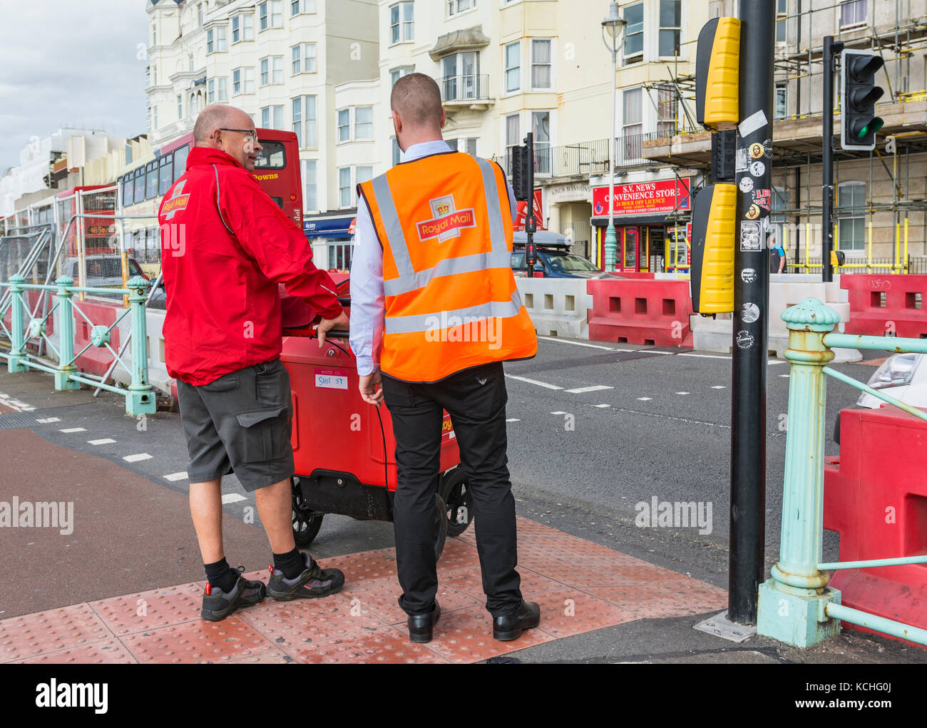 Pair of Royal Mail postmen crossing a road in a UK city. - Stock Image