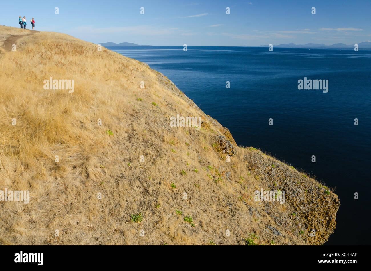 Three women gaze over the Straight of Georgia from Hornby Island, British Columbia - Stock Image