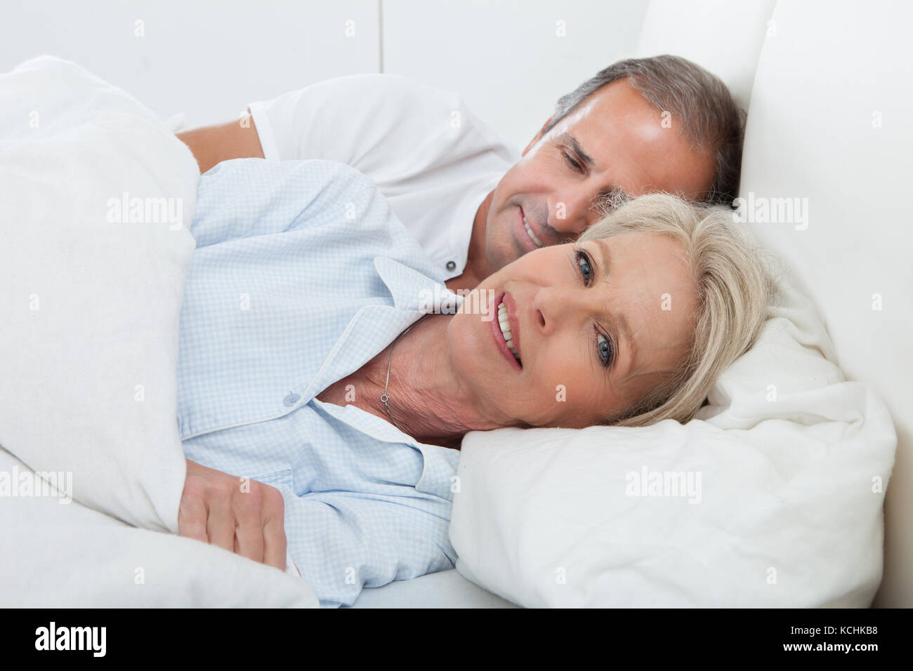 Portrait Of Happy Senior Couple Together In Bed - Stock Image