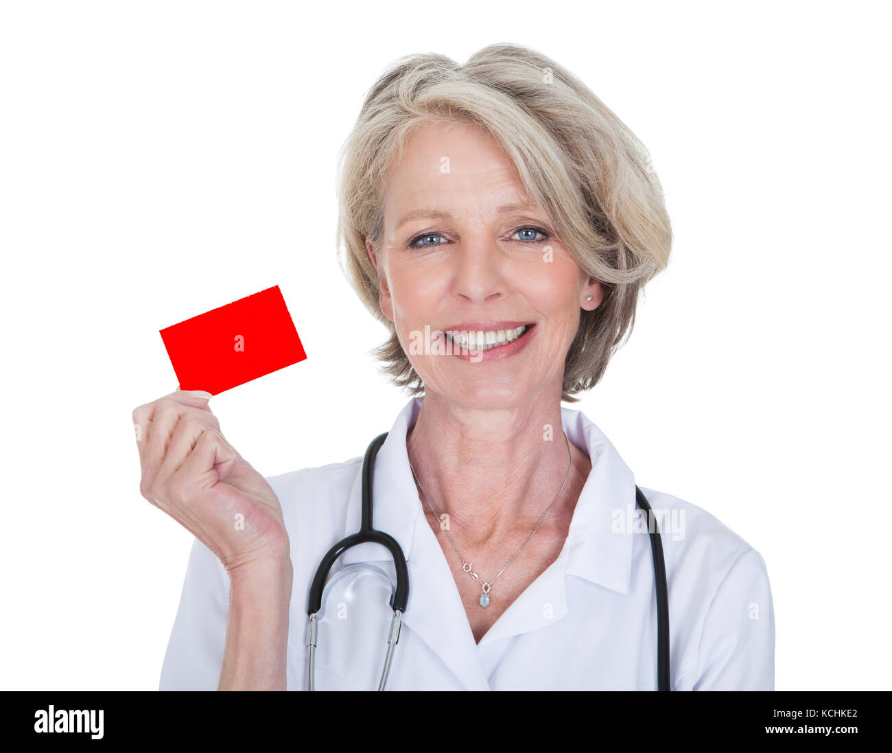 Mature Female Doctor Holding Visiting Card Over White Background - Stock Image