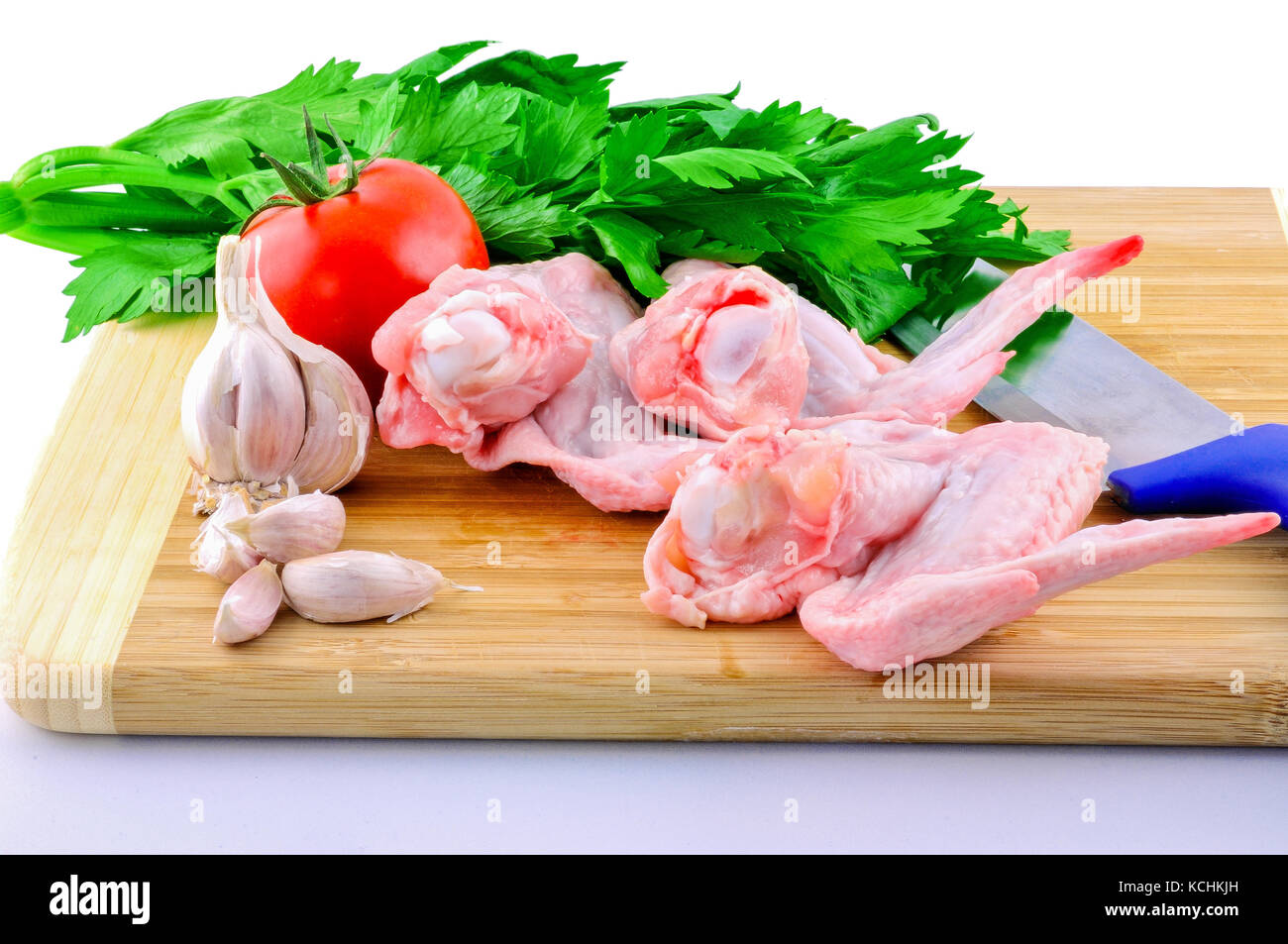 Raw chicken wings, garlic, Celler, tomato and a knife lying on a cutting board before you start to fry them - Stock Image