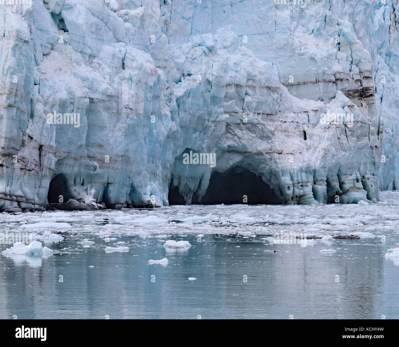 Melting ice leaves caves behind on Margerie glacier in Glacier Bay National Park and Preserve, Alaska - Stock Image