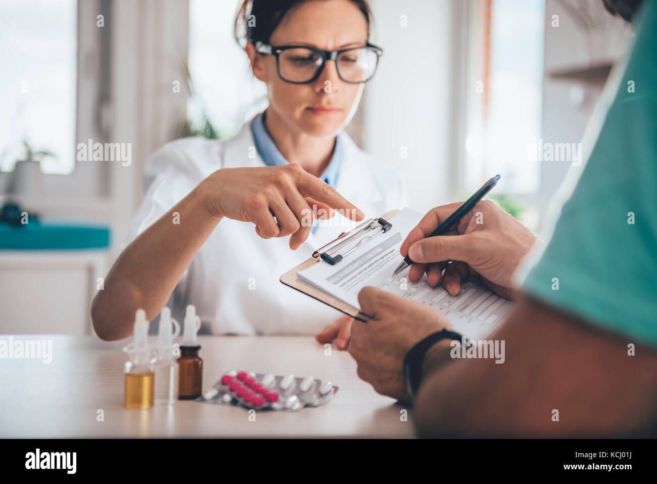 Patient filing health insurance claim form in the doctors office - Stock Image