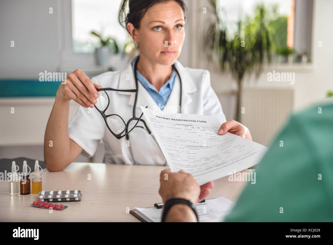 Doctor receiving patient registration form in hospital Stock Photo ...