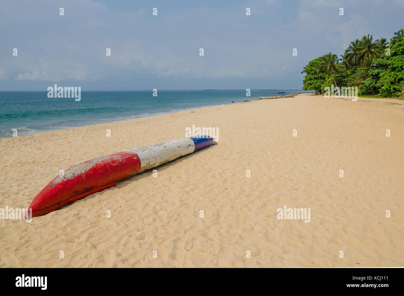 Colorful dugout fishing boat laying on deserted tropical beach at Robertsport, Liberia, West Africa - Stock Image