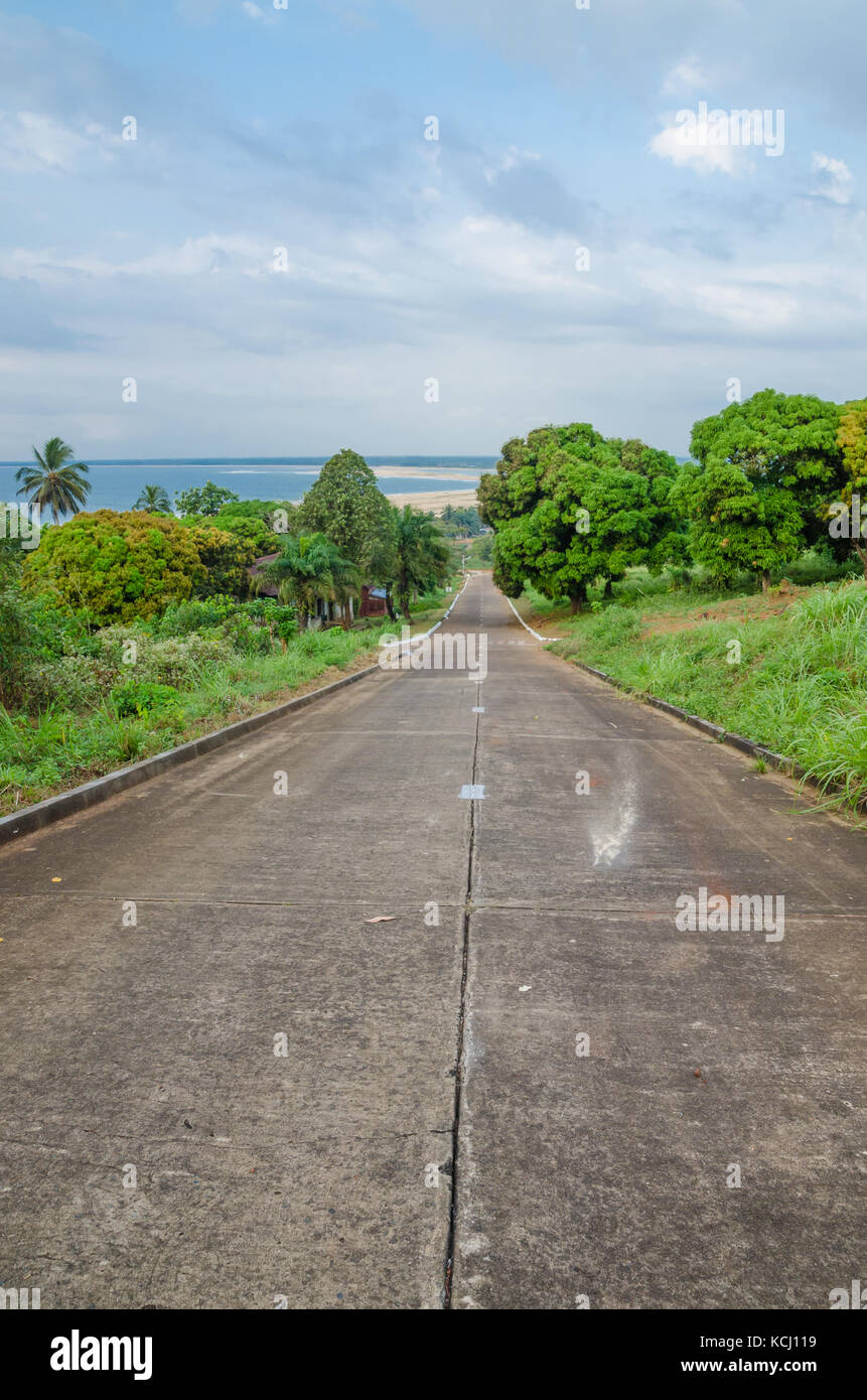 Concrete road leading down to the ocean in Robertsport, Liberia, West Africa - Stock Image