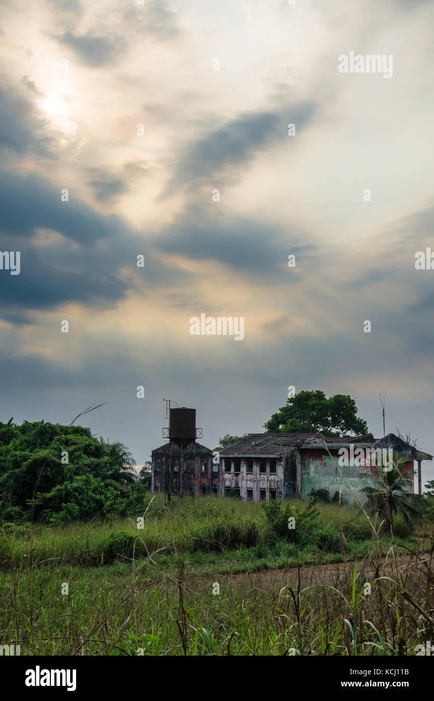 Ruined mansion surrounded by lush green with dramatic sky. Traces of the civil war in Robertsport, Liberia - Stock Image