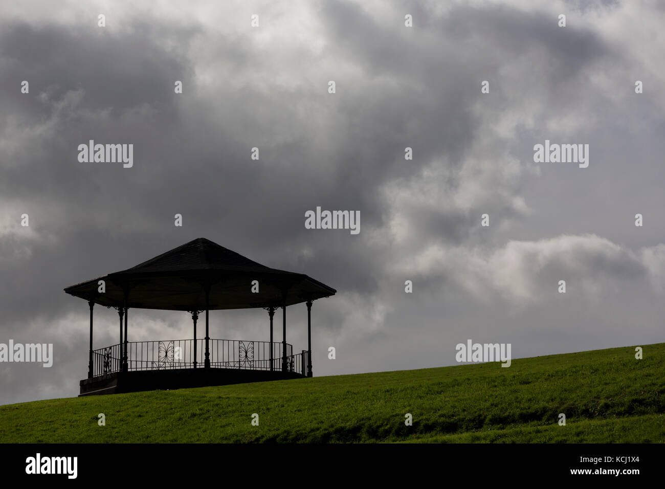 Bandstand at top of hill against dark, moody clouds in sky, green grass in foreground - Stock Image