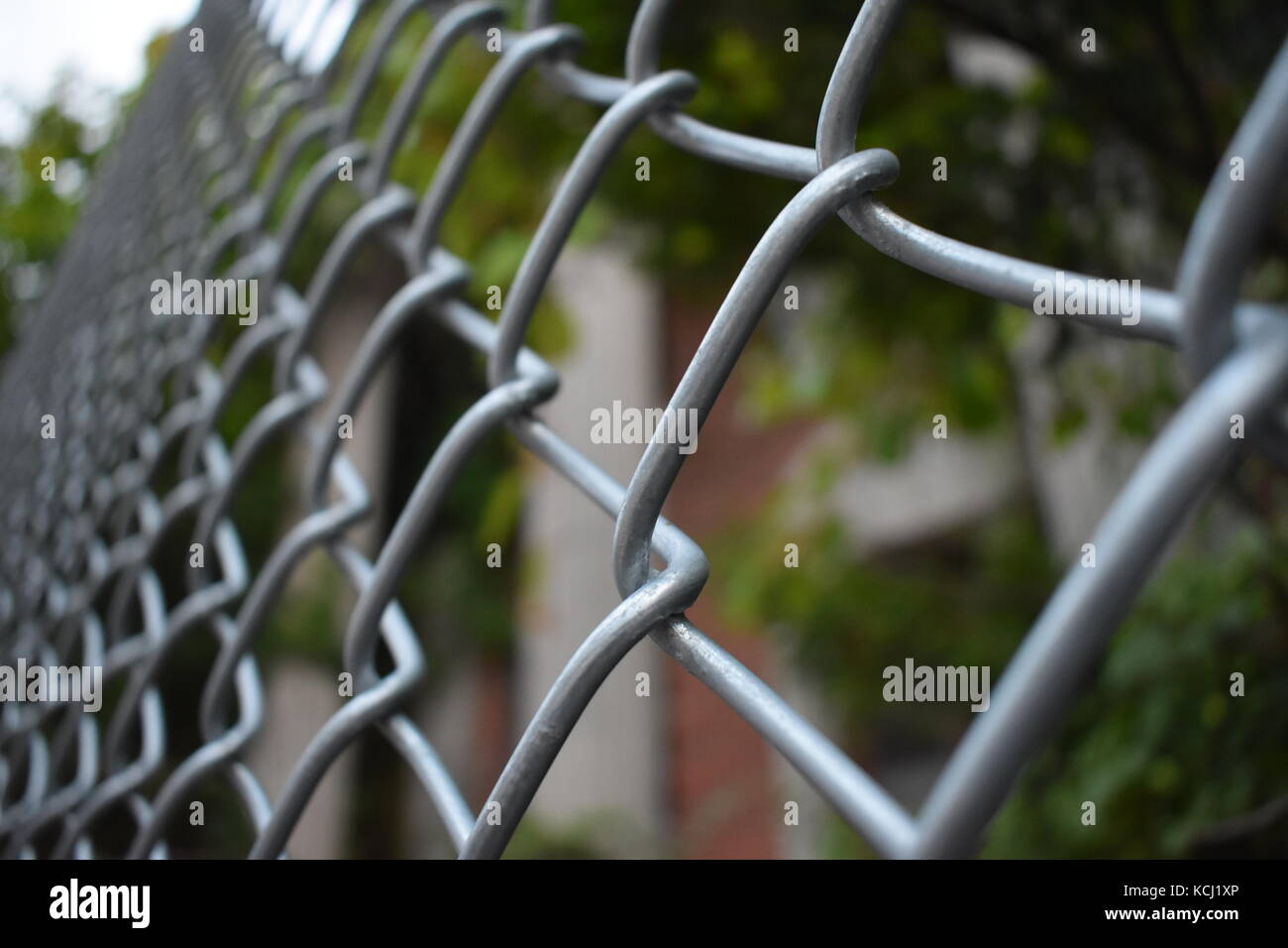 Abandoned building behind a fence - Stock Image