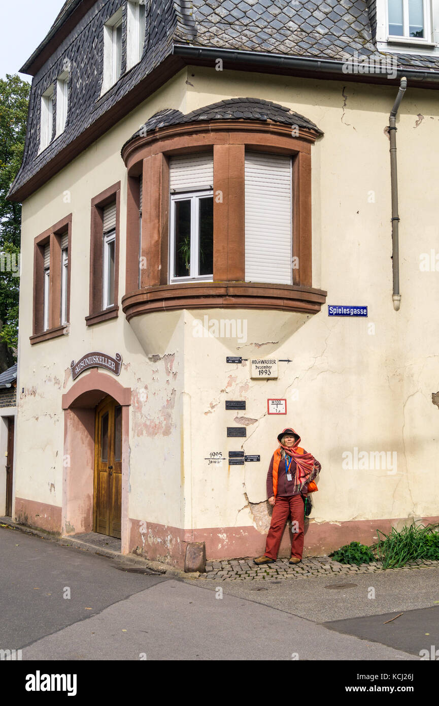 A woman in a hat next to high water (hochwasser) flood markers on a house wall,  Neumagen-Dhron, Mosel valley, Rheinland - Stock Image
