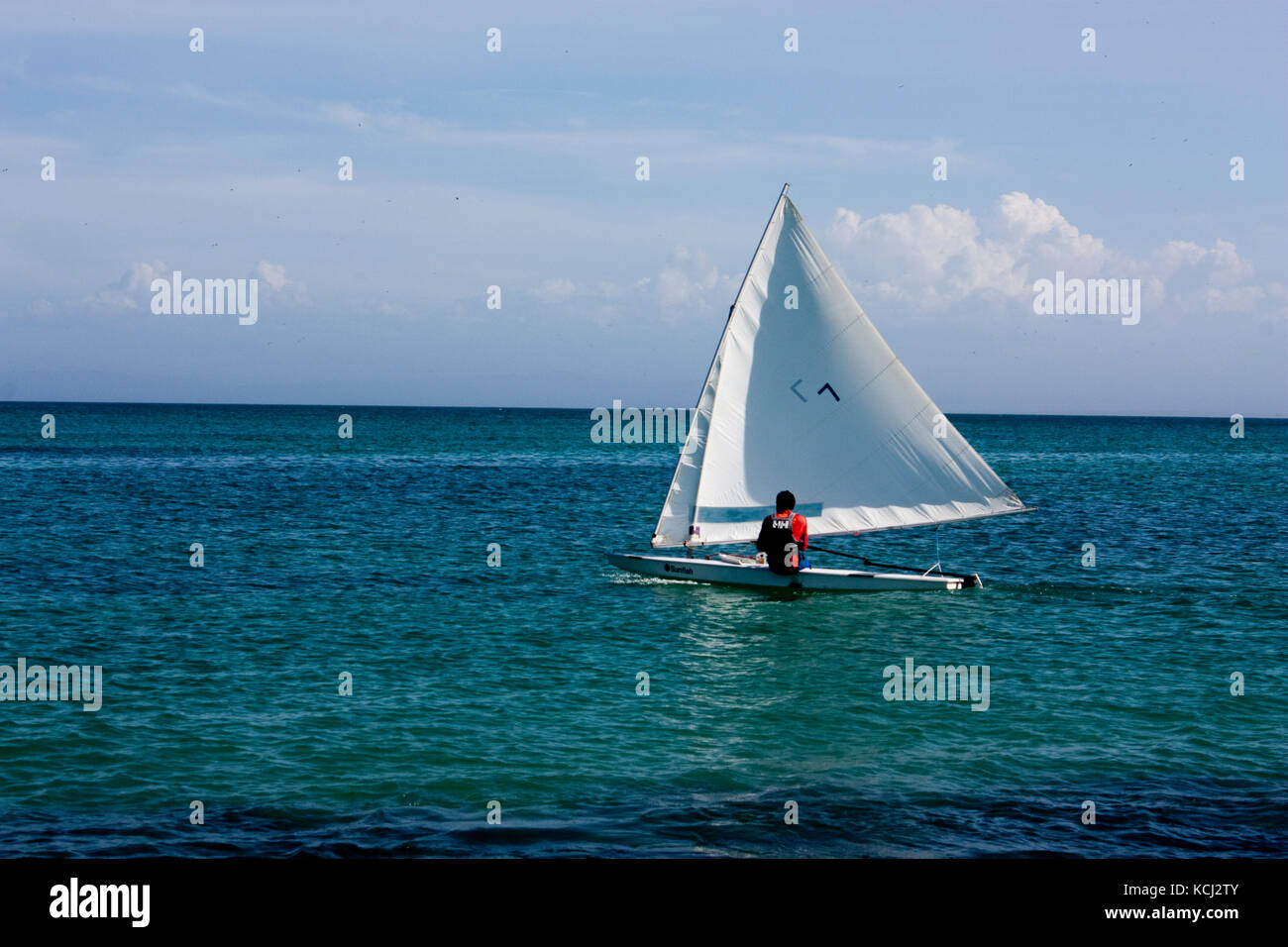 A person sails a boat on the sea in front of a beach in the island of Margarita in Venezuela Stock Photo