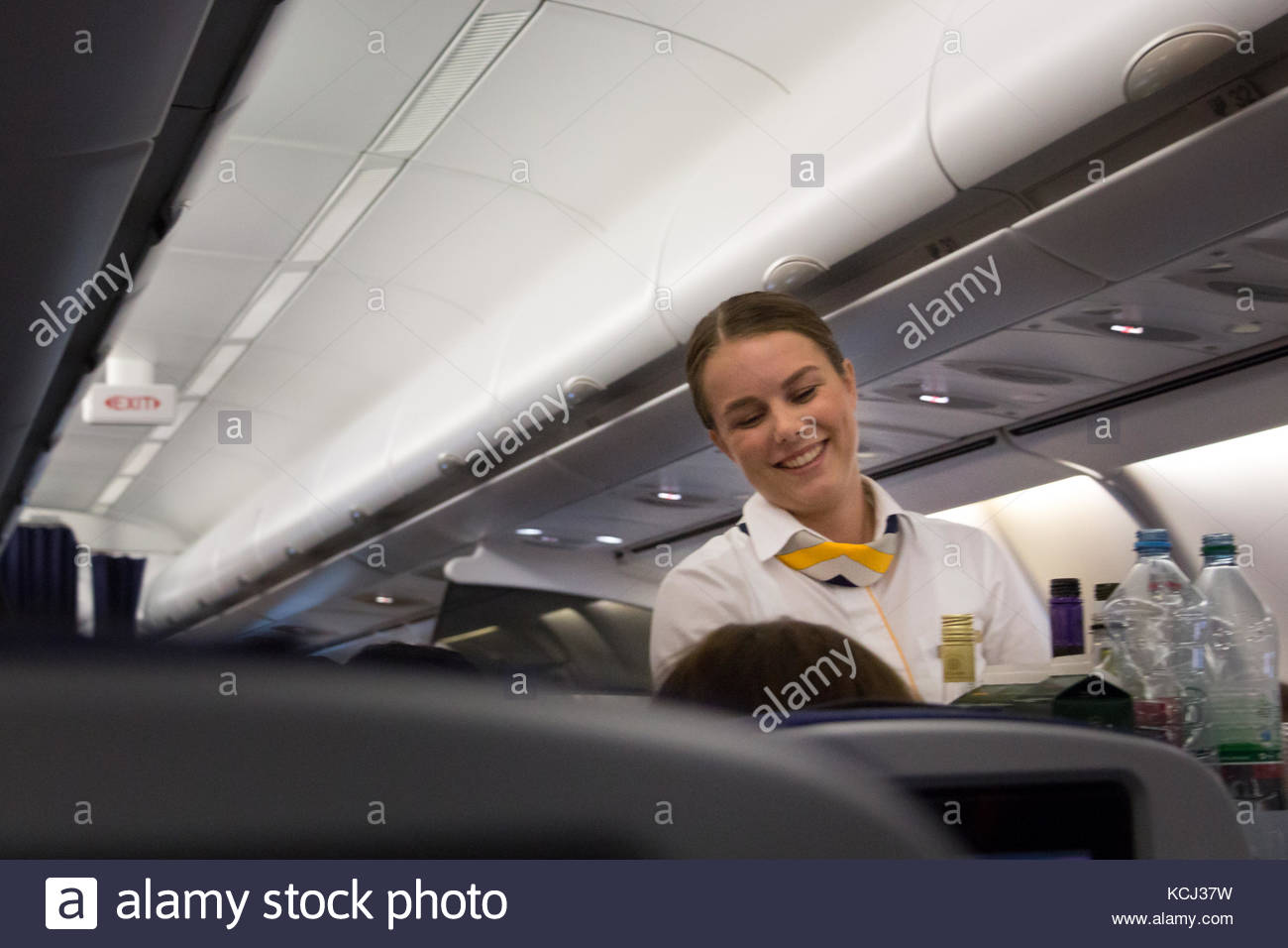 Munich, Germany - September 21th, 2017: A female flight attendant is serving the lunch to a passenger sitting in - Stock Image