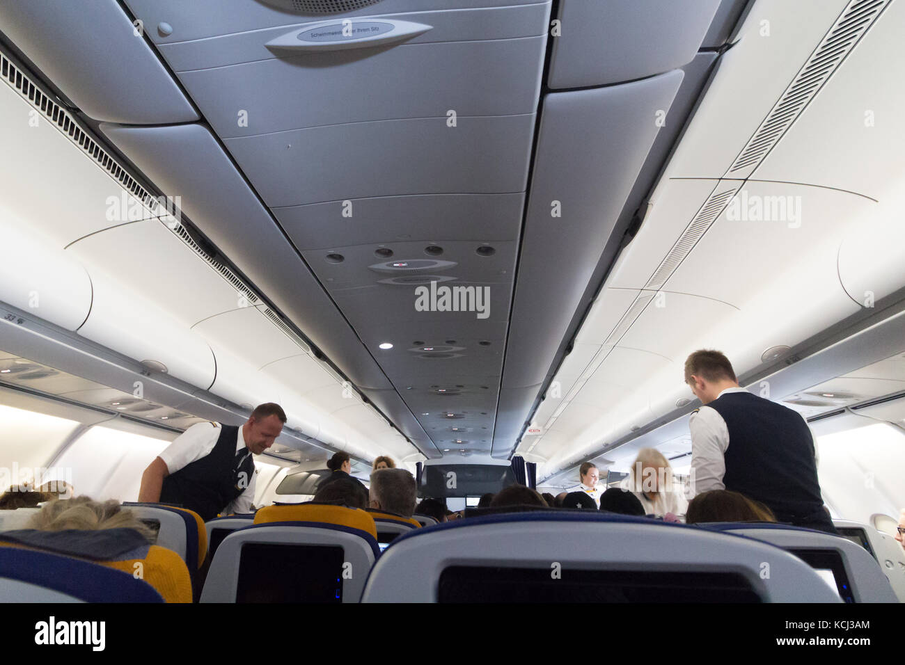 Munich, Germany - September 21th, 2017: Cabin crew is checking over the seatbelts before take off, Economy class, - Stock Image