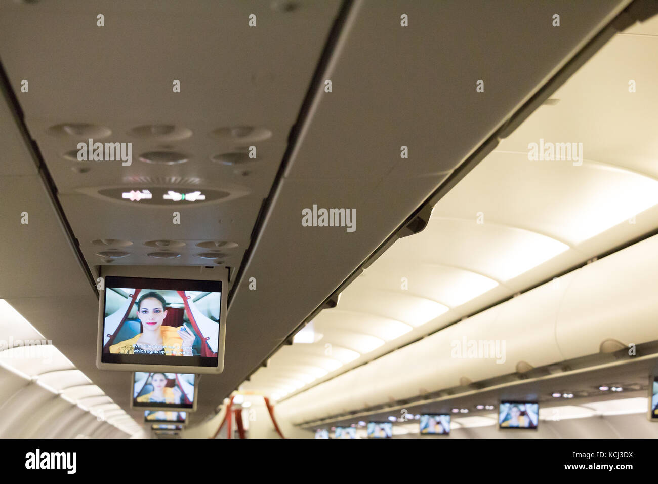 Munich, Germany, September 21th, 2017: In-flight monitors attached on the ceiling shows a flight attendant giving - Stock Image