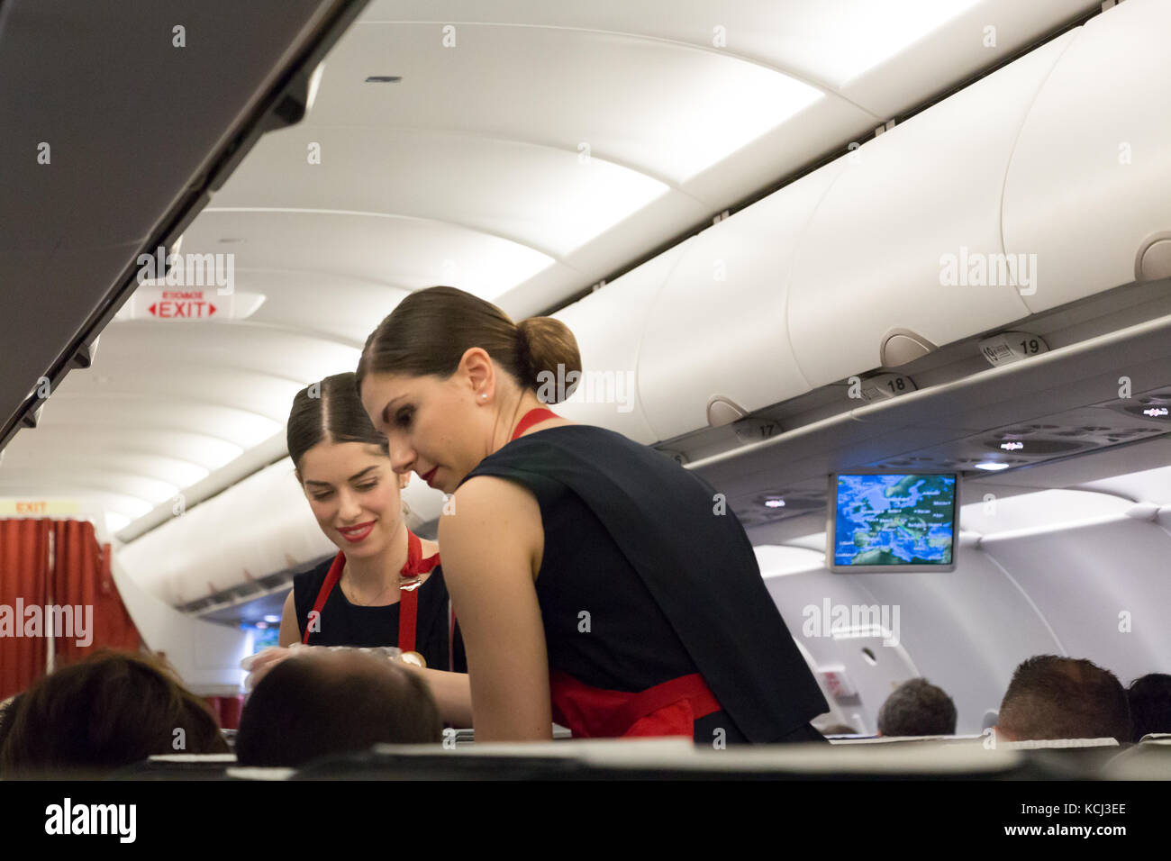 Munich, Germany - September 21th, 2017: Two female flight attendants are serving the meal in the economy class, - Stock Image